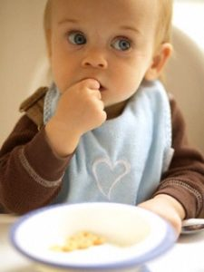 Baby Boy Eating in Highchair --- Image by © Corbis