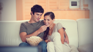 young-couple-on-the-couch-watching-a-movie-together